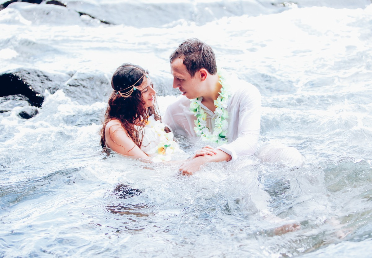 Sitting on the sandbar in the ocean in her wedding gown - photo by Kauai wedding photographer Difraser