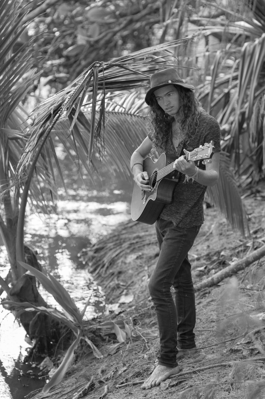 Kauai male model Steven Sedalia playing new song at river's edge.