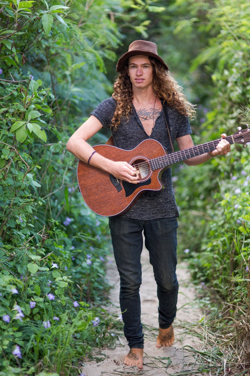 Kauai model Steven Sedalia on jungle path strumming guitar