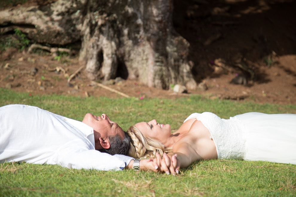 Bride and groom lying on the grass.