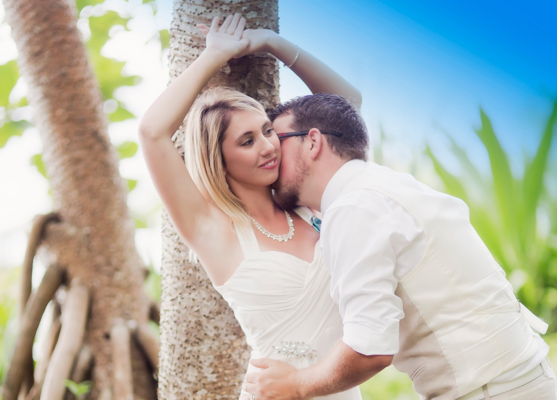 Wedding bride kissed on neck by Kauai wedding videographer Difraser