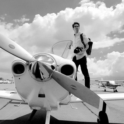 Samuel Gillilan standing on the wing of a small plane