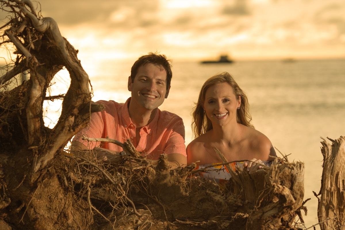 young couple posing behind fallen tree, with the sea behind them