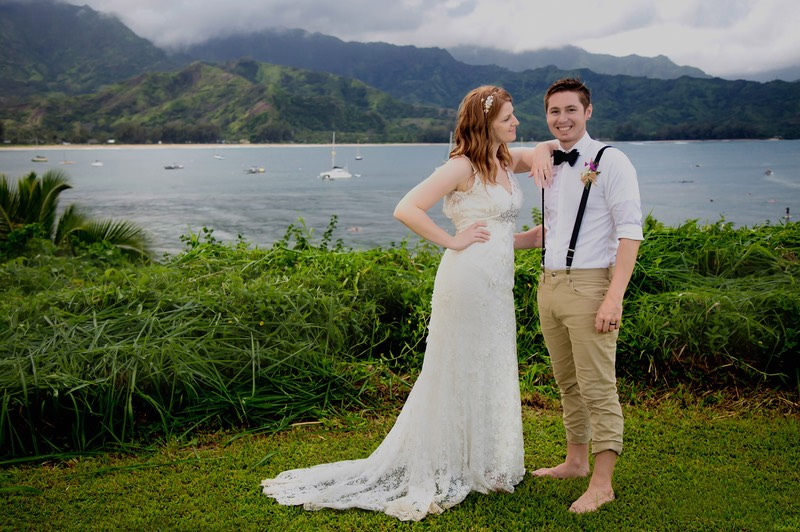 The bride's gown is rain-soaked. But it's warm rain. The grass is spongy. It's Kauai. A wedding photograph on the bluffs of Hanalei Bay.